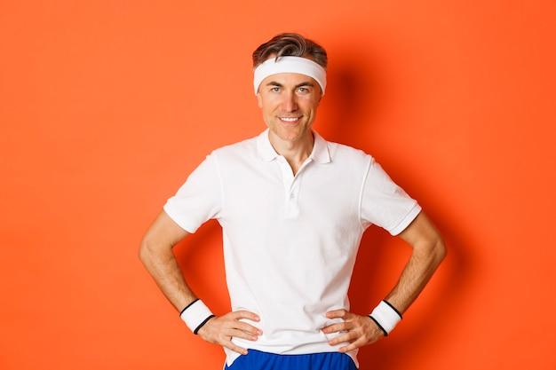 Portret van zelfverzekerde mannelijke atleet van middelbare leeftijd, die sportkleding draagt