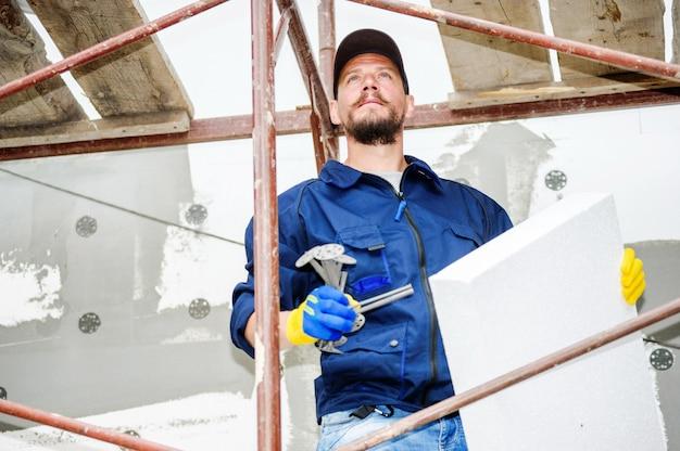 Portret van zelfverzekerde metselaar op bouwplaats.
