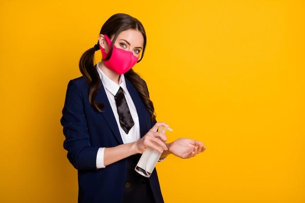 Portret van zelfverzekerde middelbare scholiere die desinfectiespray gebruikt