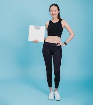 Portret van zelfverzekerde mooie aziatische fitness vrouw permanent en houden gewicht schaal na het sporten met lachend gezicht op blauwe kleur achtergrond. concept van slanke en gezonde gelukkig meisje training.