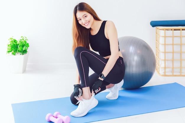 Portret van zelfverzekerde mooie aziatische fitness vrouw slijtage sportschoenen en warming-up voor oefening