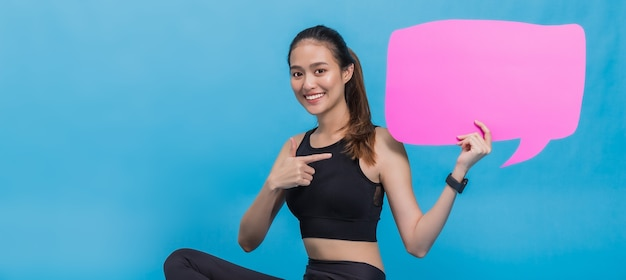 Portret van zelfverzekerde mooie aziatische fitness vrouw zitten na het sporten en lege zeepbel toespraak voor tekst op blauwe kleur achtergrond te houden. concept van slanke en gezonde gelukkig meisje training.