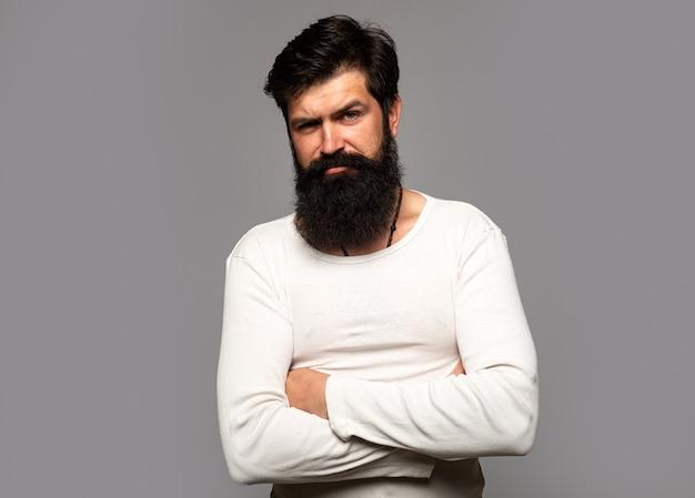 Portret van zelfverzekerde serieuze man heeft baard en snor, ziet er serieus uit, geïsoleerd. hipster kerel modellen in studio. zakenman denken met expressie op zoek. knap mannelijk model, close-upgezicht.