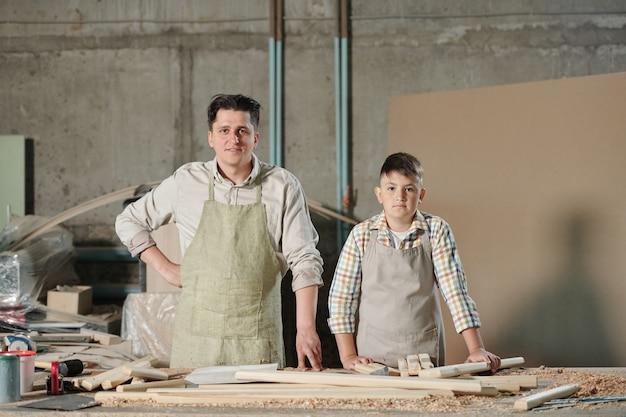 Portret van zelfverzekerde vader en zoon in schorten permanent aan bureau met houten planken in timmerwerkplaats, familiebedrijf