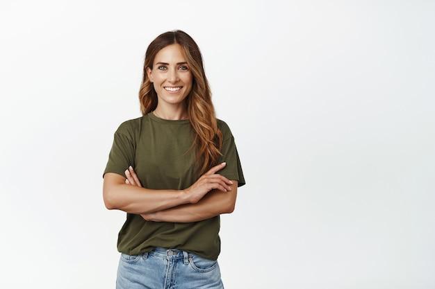 Portret van zelfverzekerde volwassen vrouw in groen t-shirt, staande met gekruiste armen op de borst en zelfverzekerde gemotiveerde glimlach, kijkend naar voren, staande tegen de witte muur.