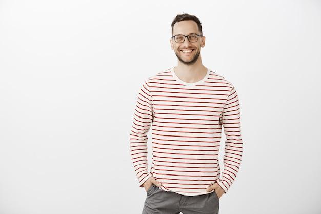 Portret van zelfverzekerde vriendelijke blanke werkgever in zwarte bril en gestreepte trui