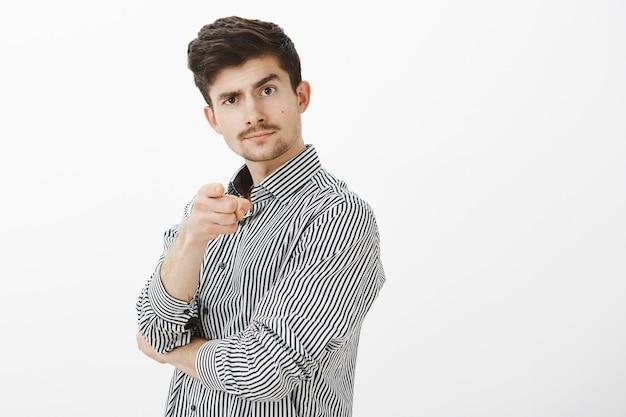 Portret van zelfverzekerde vrolijke mannelijke ondernemer met snor, wijzende en opheffende wenkbrauw, uitnodigende persoon gaat samen naar de bar, goed oogpunt bevestigen