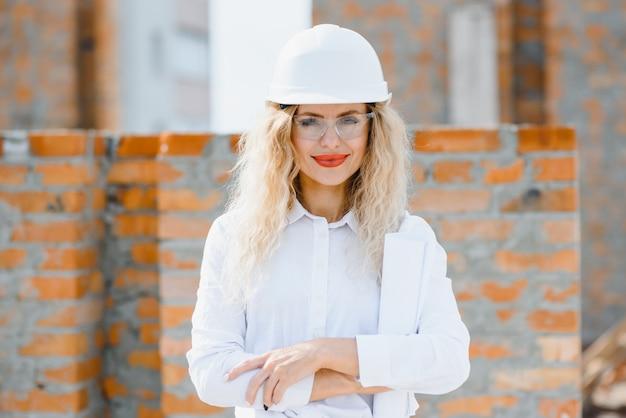 Portret van zelfverzekerde vrouwelijke bouwvakker op bouwplaats