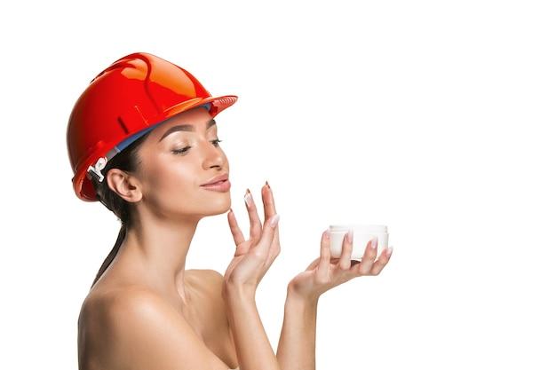 Portret van zelfverzekerde vrouwelijke gelukkig lachende werknemer in oranje helm