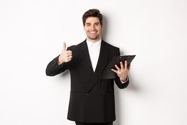 Portret van zelfverzekerde zakenman in zwart pak, klembord met documenten vasthoudend en duim omhoog in goedkeuring tonend, goed werk prijzend, staande tegen een witte achtergrond