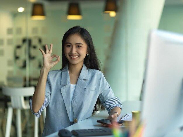 Portret van zelfverzekerde zakenvrouw glimlachend en ok gebaar tonen terwijl zittend op de werkplek