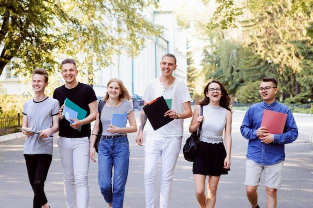 Portret van zes vrolijke vrienden die na lezing op universiteit naar huis gaan. goede vrije tijd hebben met vrienden