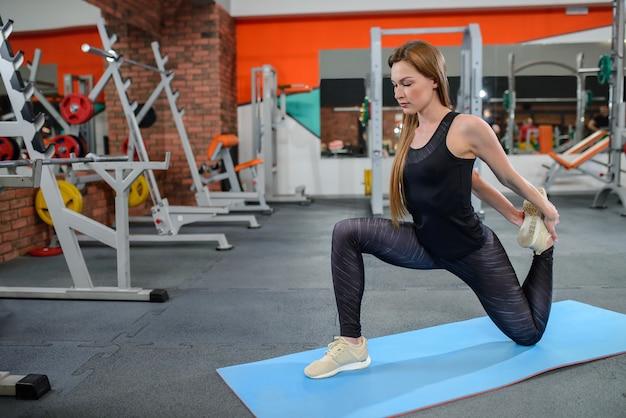 Portret van zich geschiktheidsvrouw het uitrekken bij gymnastiek vóór training