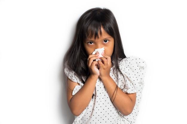 Portret van ziek aziatisch klein kindmeisje afvegen en neus met weefsel schoonmaken
