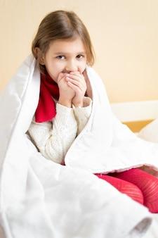 Portret van ziek meisje gewikkeld in deken hoestend in bed
