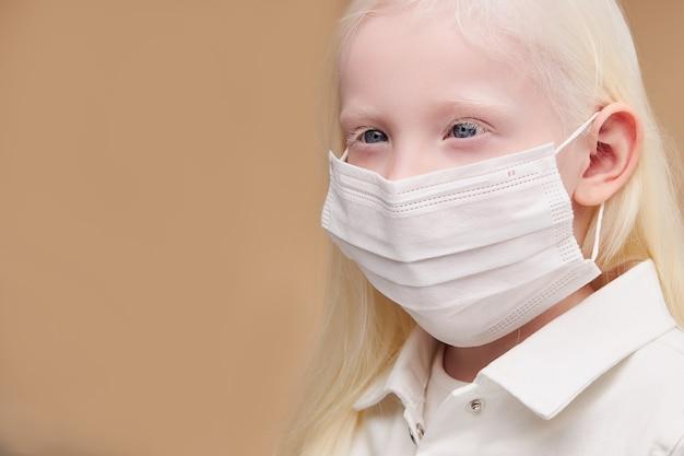 Portret van ziek mystic albinokind in medisch geïsoleerd masker