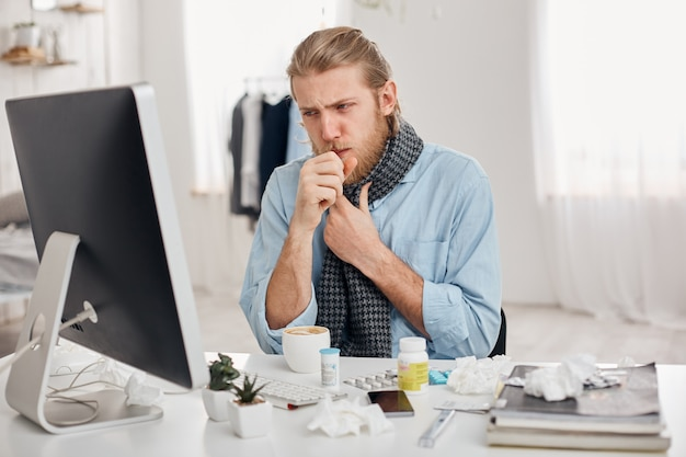 Portret van ziek zieke bebaarde mannelijke manager hoest, heeft verkoudheid en griep. jonge blonde man heeft lopende neus, hoest en ernstige verkoudheid, zit op de werkplek voor computerscherm. ziekte en infectie
