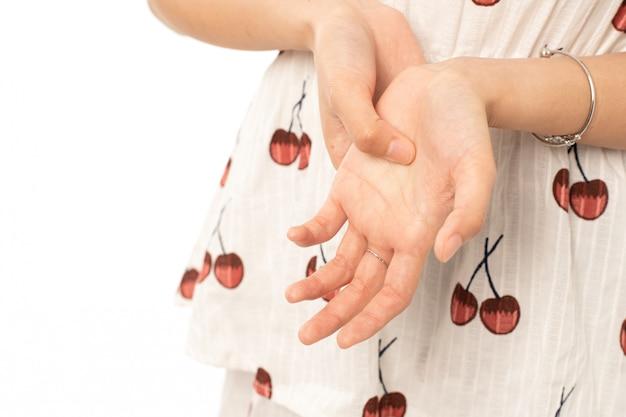Portret van zieke aziatische vrouw die aan trekkervinger lijden op witte achtergrond; vrouw masseert haar pijnlijke hand tegen symptomen van perifere neuropathie.