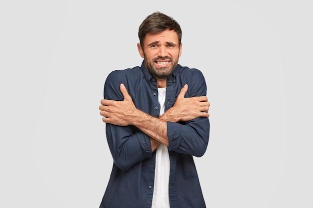 Portret van zieke bebaarde man heeft kou, beeft tijdens ijzig weer, houdt de handen gekruist, fronst gezicht met ongenoegen, gekleed in donkerblauw shirt, poseert tegen witte muur. negatief gevoel