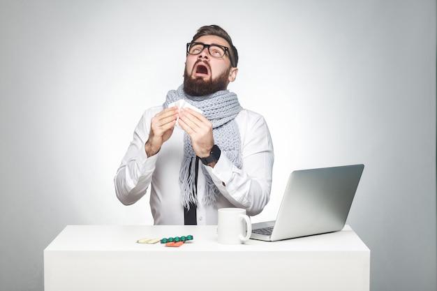 Portret van zieke, gekrabbelde jonge baas in wit overhemd, sjaal en zwarte stropdas zit op kantoor en moet een belangrijk rapport afmaken, grippe-virus hebben. studio opname, geïsoleerd, grijze achtergrond, binnen
