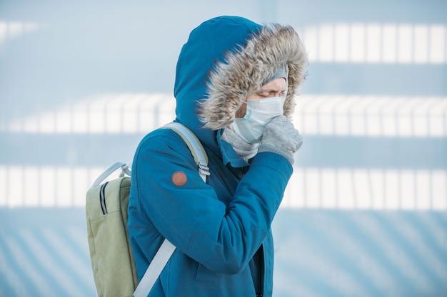 Portret van zieke jonge man in blauwe jas met capuchon, verkouden, zich onwel voelen, hoesten, medisch gezichtsmasker dragen, buitenshuis. ziekte, aankomend griepseizoen.