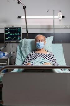 Portret van zieke senior man patiënt met chirurgisch masker rustend in ziekenhuisbed, met iv infuus bij de hand met oximeter aangesloten op vinger. moderne medische apparatuur.