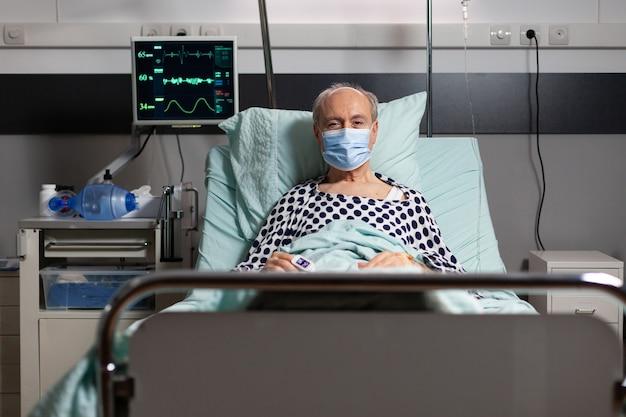 Portret van zieke senior man patiënt met chirurgisch masker rustend in ziekenhuisbed