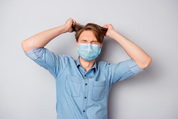 Portret van zijn aardige aantrekkelijke wanhopige verwoeste ongezonde zieke zieke man draagt een veiligheidsmasker dat gek wordt, gekke mers cov besmettingspreventie geïsoleerd over grijze kleur achtergrond