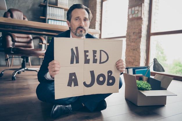 Portret van zijn depressieve werkloze man bankier zittend op houten vloer met plakkaat een baan nodig woorden bedelen nieuwe werkplek op moderne loft industriële baksteen stijl interieur werkplek werkstation
