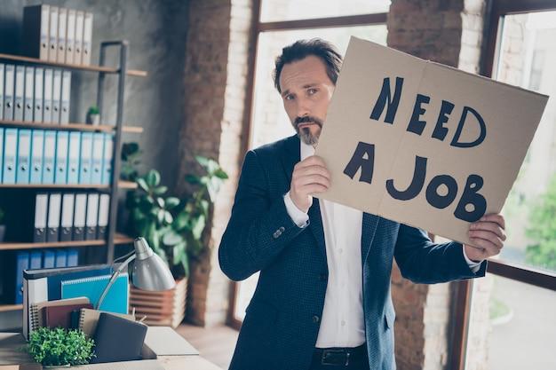 Portret van zijn depressieve, werkloze man, gekwalificeerde deskundige werkgever die een jas draagt die een plakkaat in zijn handen vasthoudt en zegt dat hij een baan nodig heeft bij een moderne loft industriële baksteenstijl interieur werkplek werkstation