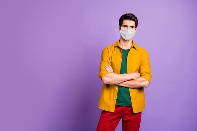 Portret van zijn gezonde kerel die een veiligheidsgaasmasker draagt, sociale afstand houdt stop mers cov griepvirus 2019 longpneumonie vaccinsyndroom gevouwen armen geïsoleerde violet lila pastelkleurige achtergrond