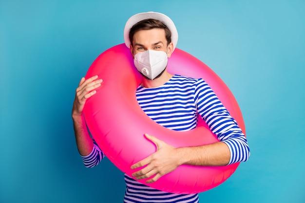 Portret van zijn hij aantrekkelijke kerel reiziger die veiligheid n95 masker draagt levensredder rubber pandemie griep decontaminatie beperking preventieve maatregelen mers cov geïsoleerde blauwe kleur achtergrond