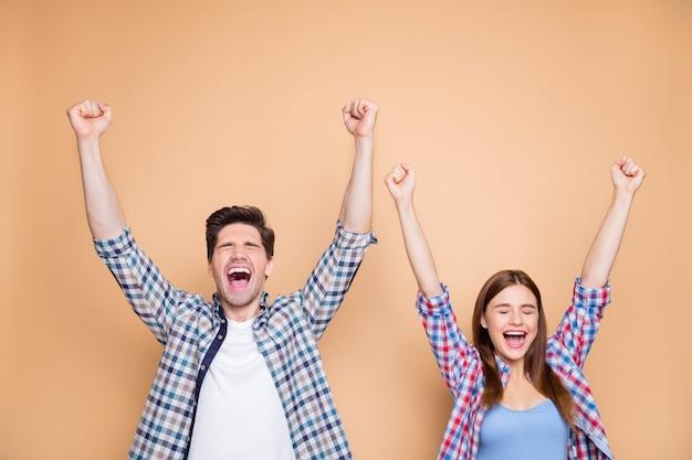 Portret van zijn hij haar ze mooi aantrekkelijk tevreden opgetogen vrolijk vrolijk paar dragen geruit overhemd vieren stijgende handen omhoog geluk geïsoleerd over beige pastel kleur achtergrond