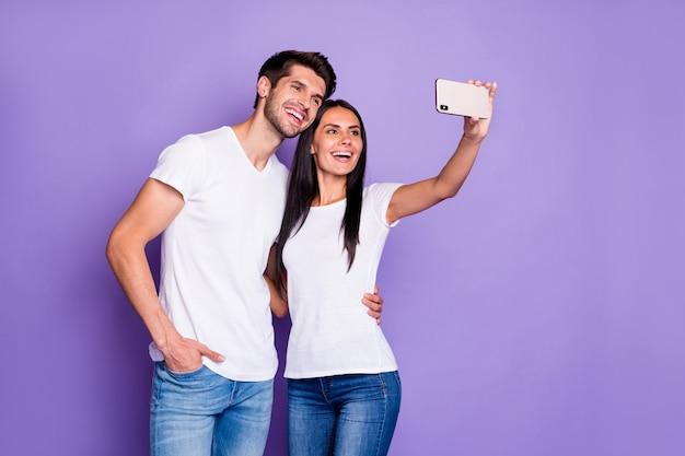 Portret van zijn hij haar ze mooie aantrekkelijke charmante mooie vrolijke vrolijk blij paar nemen selfie maken plezier vrije tijd vakantie geïsoleerd op paars violet lila kleur pastel achtergrond