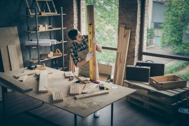 Portret van zijn hij mooie aantrekkelijke ernstige geconcentreerde gefocuste ervaren geschoolde hardwerkende man die gladheidsbord op tafel bureau bij moderne industriële loft-stijl interieurstudio controleert