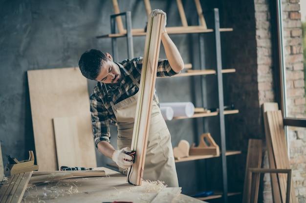 Portret van zijn hij mooie aantrekkelijke gerichte geconcentreerde professionele ervaren man deskundige houtsnijwerk creëren kastenhuis project op moderne industriële loft baksteen stijl interieur binnenshuis