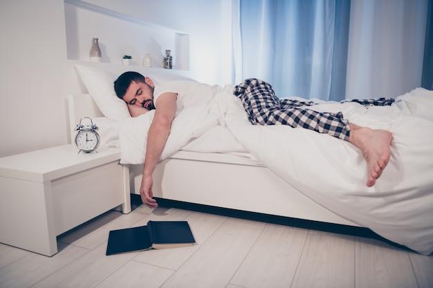 Portret van zijn hij mooie aantrekkelijke rustige vermoeide man liggend op bed in slaap gevallen na moeilijk werk dag 's nachts laat in de avond home hotel verlicht kamer plat huis