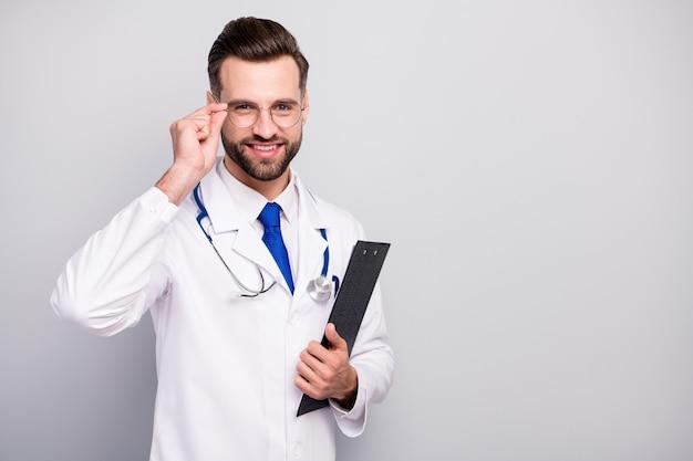 Portret van zijn hij mooie aantrekkelijke vrolijke vrolijke doc arts in de hand houden document klembord aanraken specs ehbo-assistent geïsoleerd op licht wit grijs pastel kleur