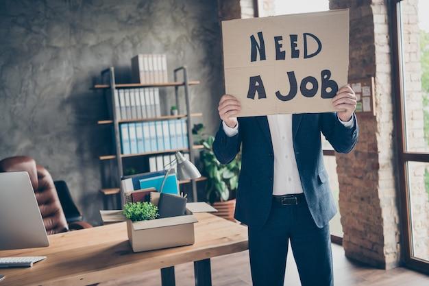 Portret van zijn hij werkloze man gekwalificeerde ceo baas chef haai met in handen plakkaat te zeggen dat hij een baan nodig heeft crisisindustrie op moderne loft industriële baksteen stijl interieur werkplek werkstation