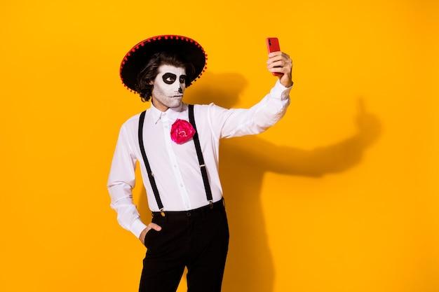 Portret van zijn mooie geschilderde griezelige serieuze imposante kerel caballero vriendje nemen selfie calavera catrina look outfit geïsoleerd helder levendig glans levendige gele kleur achtergrond