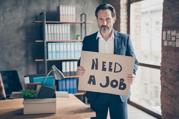 Portret van zijn serieuze werkloze makelaar-econoom die in handen een plakkaat vasthoudt en zegt dat hij een baan nodig heeft, zoek een oplossing bij een moderne loft, industriële baksteenstijl interieur werkplek werkstation