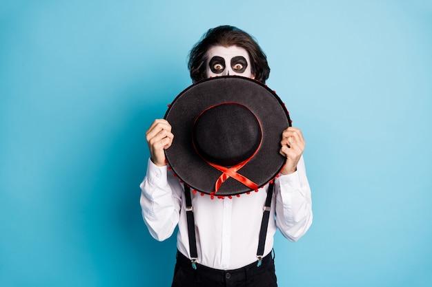 Portret van zijn stijlvolle imposante verbaasde verbijsterde bange kerel heer vreemdeling verbergt gezicht achter sombrero spookachtig carnaval geïsoleerd helder levendig glans levendige blauwe kleur achtergrond