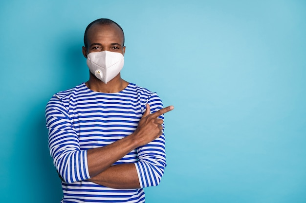 Portret van zijn tevreden gezonde kerel die veiligheidstrend n95-ademhalingsmasker draagt dat exemplaar lege ruimte aantoont stop mers cov griepgriep geïsoleerd over blauwe kleurenachtergrond
