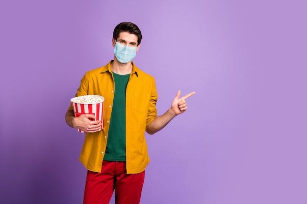 Portret van zijn tevreden man met veiligheidsgaas herbruikbaar masker dat maïs eet en demonstreert kopieerruimte stop virale mers cov griepgriep grippe geïsoleerde violet lila pastelkleurige achtergrond