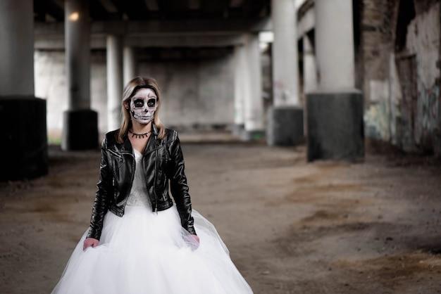 Portret van zombievrouw met geschilderd schedelgezicht onder een brug.