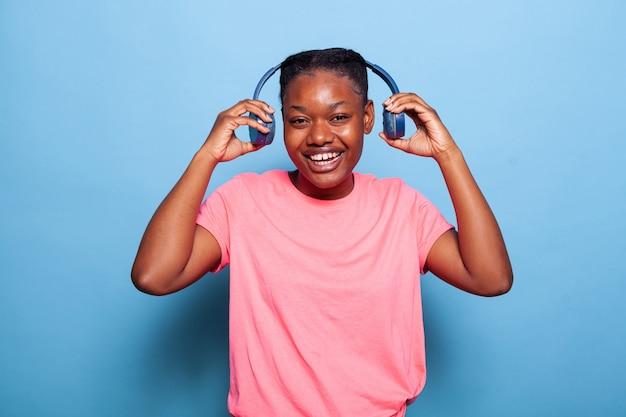 Portret van zorgeloze afro-amerikaanse jonge vrouw die een koptelefoon zet