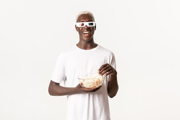 Portret van zorgeloze glimlachende afro-amerikaanse man, film kijken in 3d-bril en popcorn eten, genieten van bioscoop