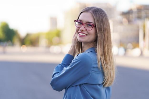 Portret van zorgeloze jonge vrouw die lacht met stedelijke straat. vrolijk kaukasisch meisje dat een bril draagt in de stad.