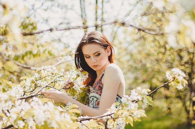 Portret van zorgeloze jonge vrouw in boho-stijl jurk in de lentetuin van de kersenbloesem.