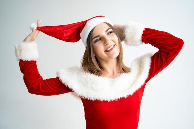 Portret van zorgeloze vrouw in santa claus jurk spelen met hoed